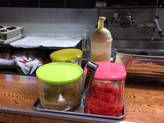 カウンターの上には紅生姜や魚粉、刻みニンニク、マヨネーズが置いてあります