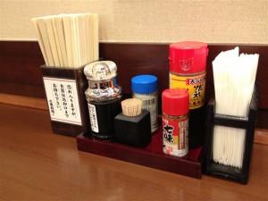 テーブルには箸の他、釜玉うどん用の醤油、天ぷら用だしソース、七味や塩などが置いてある